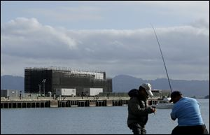 Two men fish in the water in front of a barge on Treasure Island in San Francisco. Google is erecting a four-story structure in the heart of the San Francisco Bay but is managing to conceal its purpose by constructing it on docked barges instead of on land, where city building permits and public plans are mandatory. Construction became obvious a few weeks ago.
