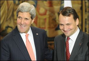 U.S. Secretary of State John Kerry, left, and Polish Foreign Minister Radek Sikorski share a light moment after a news conference following their talks in Warsaw, Poland.