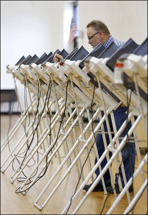 Dave Fitzpatrick looks over his choices as he casts his vote at Garfield Elementary in East Toledo. Only a quarter of Lucas County's registered voters turned out Tuesday.