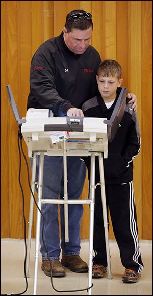 Rob Marquette shows his son Dominic, 10, how to vote at St. Paul's Episcopal Church in Oregon.