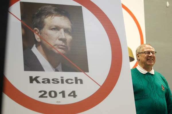 D-Michael-Collins-stands-next-to-an-anti-Kasich-sign