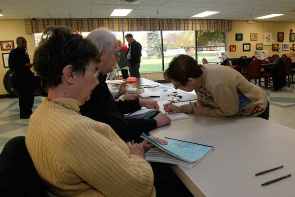 Poll-workers-Jill-left-and-Art-Keller-as-voter-M
