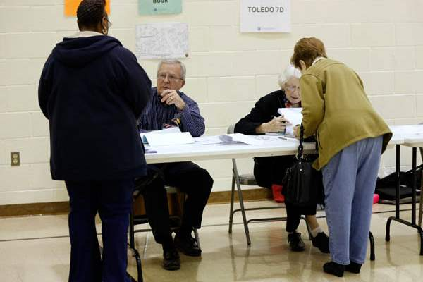 Poll-workers-John-Dougherty-left-and-Joanne-Moore-check-in-voters
