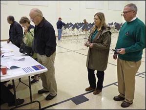 CTY collinsvotes06p  Toledo mayoral candidate D. Michael Collins, right, and Sandra Drabik, his wife, wait to check-in to vote at the polling place at Church of the Cross on Cass Road, on election day, Tuesday, November 5, 2013.  The Blade/Dave Zapotosky