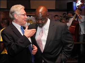 Campaign consultant Mark Luetke, left, confers with Toledo Mayor Mike Bell during election night party at Table 44 in Toledo, Ohio.