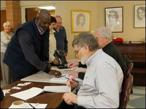 Mayor Mike Bell, left, signs in before voting.
