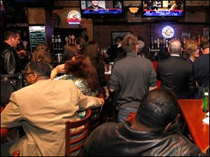 Mayor Mike Bell supporters watch the multiple televisions during Bell's election night party at Table 44 in Toledo, Ohio.