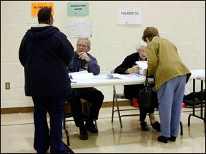 Poll workers John Dougherty, left, and Joanne Moore check-in voters.