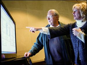 TPS board member Lisa Sobecki points to a screen showing results along with Sylvania resident Stan Odesky.