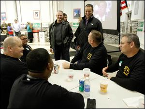 The Toledo Police Patrolman's Association Union President Dan Wagner, center standing, speaks with a table of law enforcement.