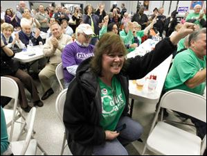 Volunteer and supporter Tina Scott raises her arms in victory during the D. Michael Collins election viewing party.