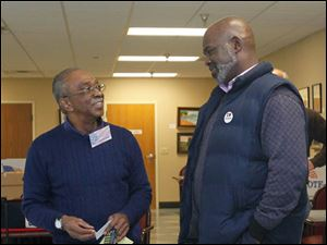 Poll worker Eddie Squaires, J.D., left, talking with Mayor Mike Bell while he waits to vote.