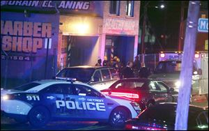 Police gather at a scene of a multiple shooting at Al's Place Barber Shop, Wednesday, in Detroit.