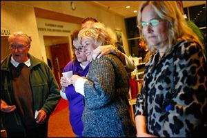 TPS spokesperson Patty Mazur, left, hugs board member Lisa Sobecki as they watch results along with Sylvania resident Stan Odesky and board candidate Polly Taylor-Gerken.