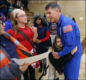 Astronaut Shane Kimbrough gets a hug from kindergartner Mavric Smith as he speaks with fifth-grader Heather Shiffler, left, fifth-grader Jada Callahan, center, and others at Discovery Academy.