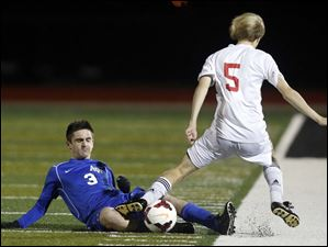 Anthony Wayne's Jared Russell (3) moves the ball against  Mentor's Alan Wardeiner (5).
