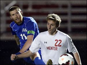 Anthony Wayne's Ben Conkin (11) kicks the ball against  Mentor's Jeff Davis (22).