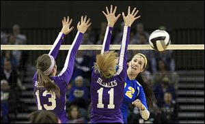 St. Ursula's Lauren Daudelin, right, hits the ball past Columbus DeSales players Kendall Witt, left, and Emily Durbin. Daudelin finished with 10 kills.
