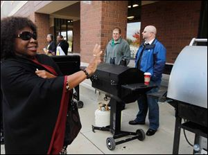 Dr. Connie Okoye-Nantwi, from Reynolds Elementary, left,  waves and smiles at school district members manning the grill.