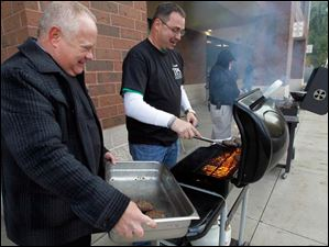 Andy Frank, left, and Jim Gault, right, grill up burgers for TPS teachers and staff during Staff Appreciation Day.