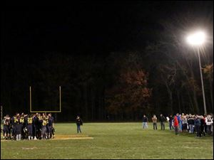 As their family and friends wait along the sidelines, Whiteford's team gather together on the field after the win.