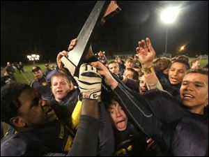 Whiteford's football team swarms their trophy after the win.