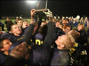 Whiteford9p Whiteford's senior Christopher Sims, left, closes his eyes as he holds his team's trophy aloft.