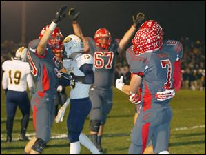 Bedford High School player Connor Clements (7) celebrates with teammates after scoring an early touchdown against Saline.