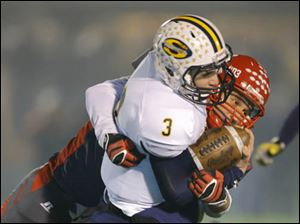 Bedford High School player Ivan Oraha (44) tackles Saline High School player Trent Theisen (3).