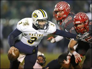Saline High School quarterback Trent Theisen (3) tries to turn the corner against the Bedford High School defense.
