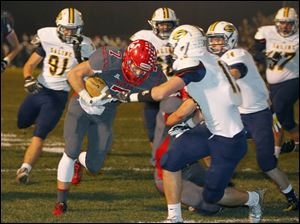 Bedford High School player Connor Clements (7) bulls his way into the end zone for a touchdown against Saline High School player Chris Terech (10) during the first quarter.