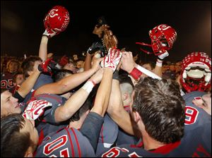 Bedford High School players celebrate with their District Championship trophy after defeating Saline High School.