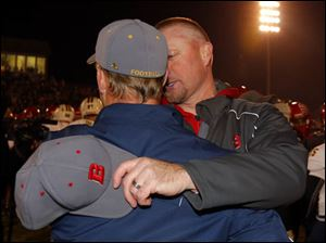 Bedford High School head coach Jeff Wood, right, speaks with Saline High School head coach Joe Palka after their football game.