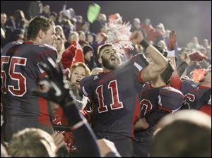 Bedford High School players, including Cole Hoffman (55) and Alec Hullibarger (11) celebrate their win with fans.