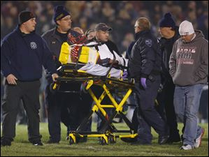 Bedford High School player Connor Clements (7) is taken from the field after being injured against Saline High School during the fourth quarter.