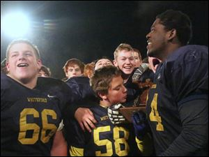 Whiteford's freshman Jordan Koth (58) kisses his team's trophy after the win.