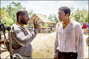 Director Steve McQueen, left, discusses a scene with lead actor Chiwetel Ejiofor on the set of  '12 Years a Slave.'