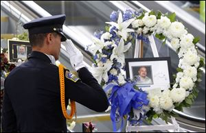 TSA officer Fritz Corros salutes at Los Angeles International Airport, during a moment of silence today  to honor the Transportation Security Administration officer Gerardo Hernandez, killed by a gunman at the airport a week ago.