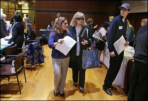 Maura Mazzocca attends a job fair for the visually impaired with the aid of volunteer guide Kate Loosian, left, at Radcliffe Yard in Cambridge, Mass.