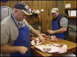 Paul De Land, left, jokes with his brother Steve De Land as they trim and cut beef behind the counter.