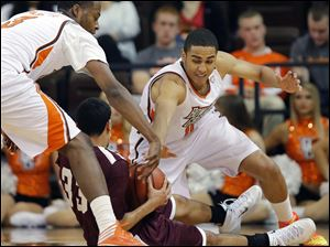 Bowling Green State University center Josh Gomez (0) and forward Spencer Parker (3) battle Earlham guard Michael Parker (33) for the ball.