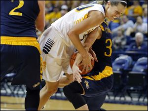 University of Toledo player Stephanie Recker (20) tries to drive between Drexel University players Abby Redick (2) and Fiona Flanagan (33)  during the second half.