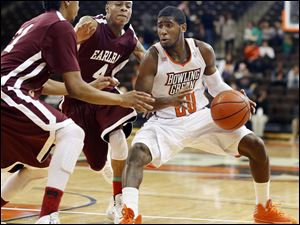 Bowling Green State University guard Jehvon Clarke (20) drives against Earlham forward Phillip Boone (21) and guard Vadial Jett (4).