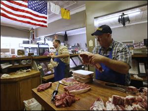 Steve De Land, left, fills a customer's order from the counter while Paul De Land, right, carves and packages beef.