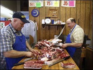 Paul De Land, left, jokes with his brother Steve De Land, right, as they process beef behind the counter.