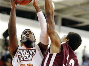 Bowling Green State University guard Jehvon Clarke (20) takes a shot against  Earlham forward Kristian Barden (32).