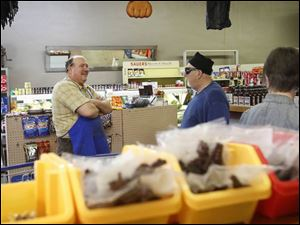 Steve De Land, left, talks with customers at Milo's Meat Market in North Toledo.