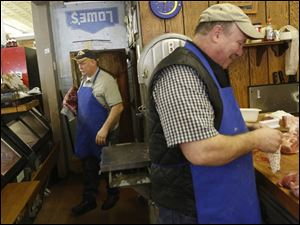 Paul De Land, left, grabs a cut of meat from inside the locker as his brother Steve De Land, right, packages cuts of beef behind the counter.