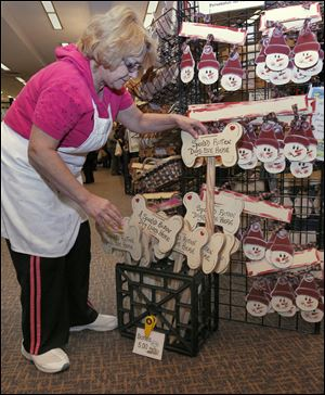 Susan Santana of Walbridge stocks her booth with dog-bone-shaped signs at the Toledo show. She is one of the more than 80 exhibitors.