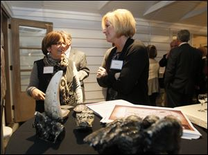 Imagination Station foundation officer Shelly Orenstein, left, speaks with Kelly Hart about Bones: Dinosaurs Uncovered, one of the three proposed exhibits the group is considering funding. At left in front is a tooth from Tyrannosaurus Rex, and at right, teeth from a mastodon.